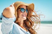 Side view of beautiful mature woman wearing sunglasses enjoying at beach. Young smiling woman on vacation looking away while enjoying sea breeze wearing straw hat. Closeup portrait of attractive girl