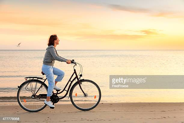 Mature woman with bike on beach at sunset