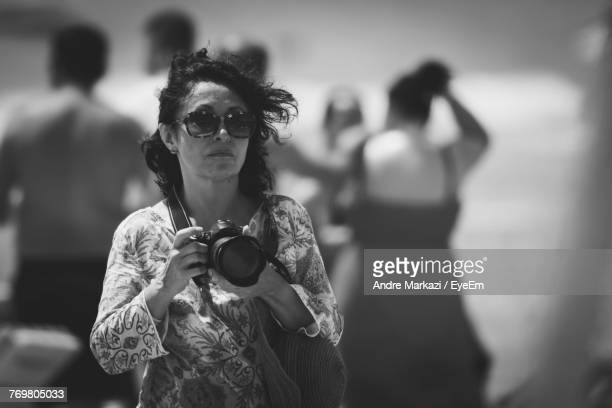 Mature Woman With Camera Standing At Beach