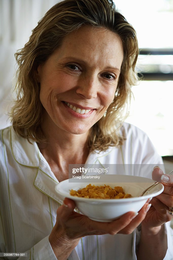 Mature woman with cereal bowl, portrait, close-up : Stock Photo