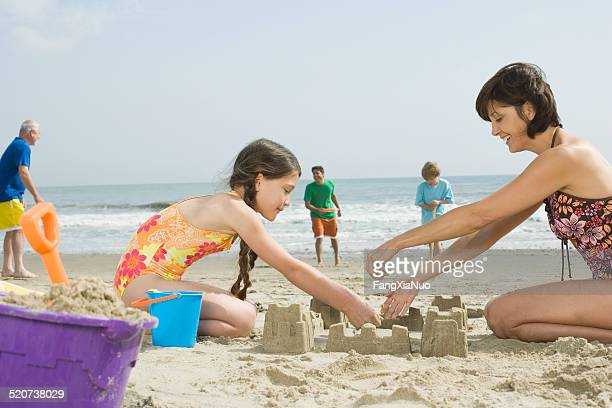 Mature woman with daughter (8-9) making sand castle on beach