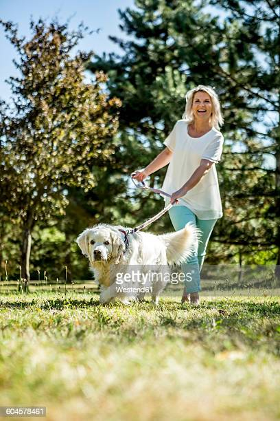 Mature woman with dog on a meadow