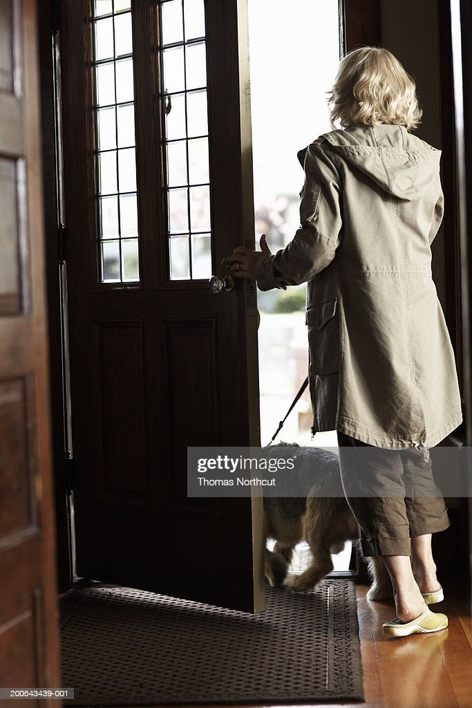 Mature woman with dog on leash walking out front door, rear view : Stock Photo