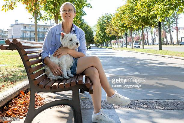 Mature woman with dog on the bench