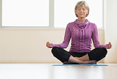 Full length of mature woman with eyes closed sitting in lotus position at home