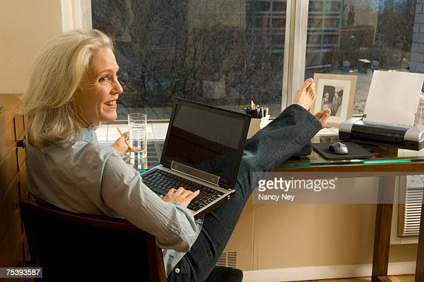 Mature woman with feet up, working on laptop