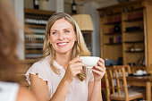 Mature woman holding coffee cup and talking with her friend. Beautiful woman smiling and sitting at a table and drinking a cappuccino. Happy senior woman having breakfast at cafeteria.