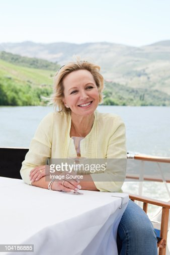 Mature woman with glass of wine on a boat holiday