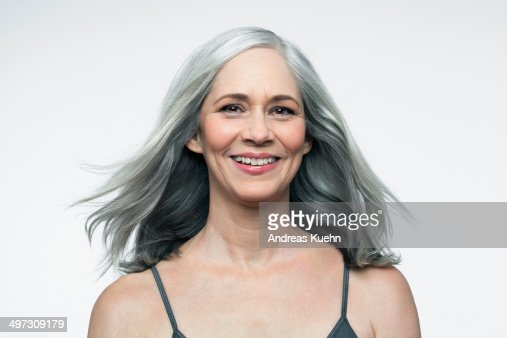 Mature woman with grey hair smiling, portrait.