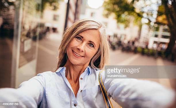 中年の女性、グレーのヘアセルフィーを取る city street