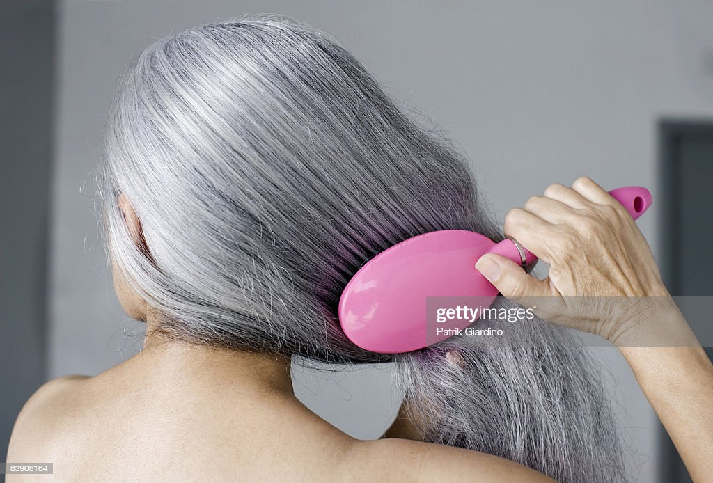 Mature woman with hair brush : Stock Photo