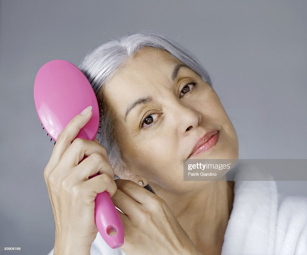 Mature woman with hair brush : Stock Photo