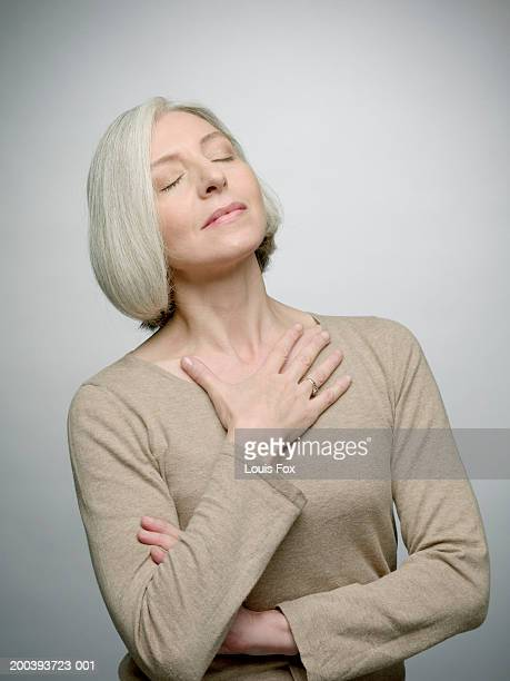 Mature woman with hand on chest, eyes closed