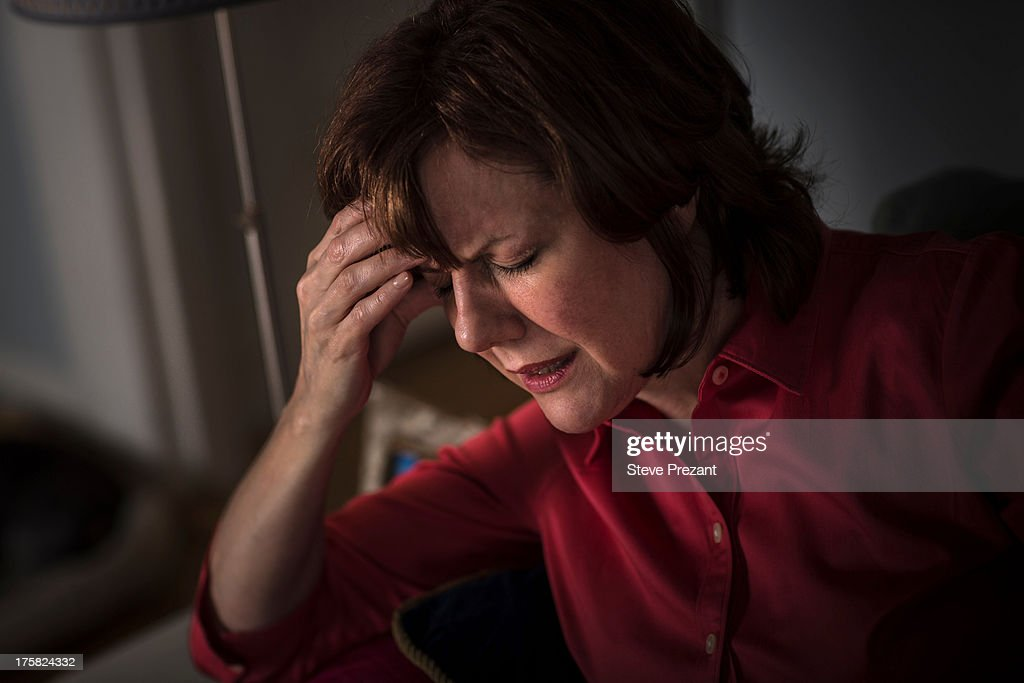 Mature woman with hand on head and eyes closed : Stock Photo