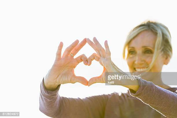 Mature woman with hands in shape of heart