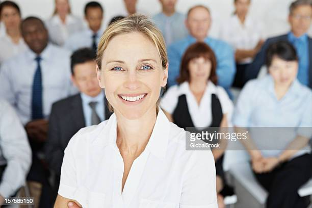 Mature woman with her business colleagues in the background