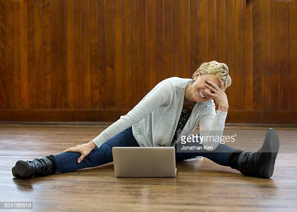 Mature woman with laptop on floor.