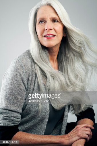 Mature woman with long, gray hair looking away. : Stock Photo