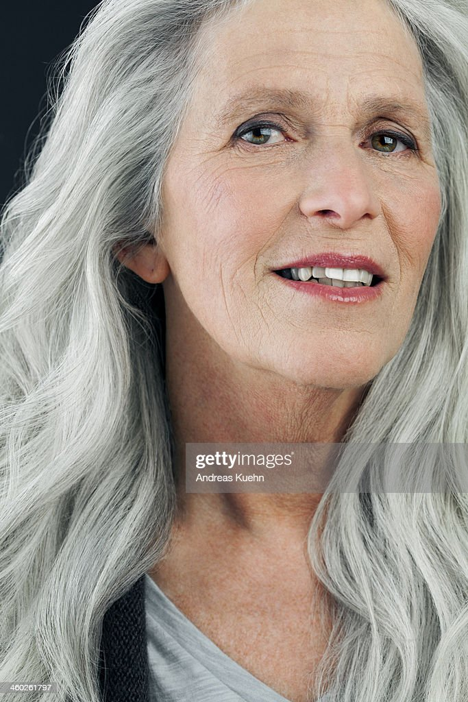 Mature woman with long, gray hair smiling. : Stock Photo
