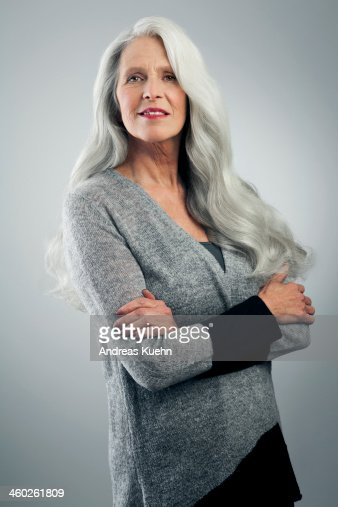 Mature woman with long, gray hair, standing.