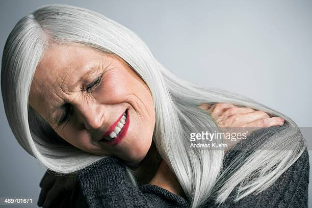 Mature woman with long grey hair hugging herself.
