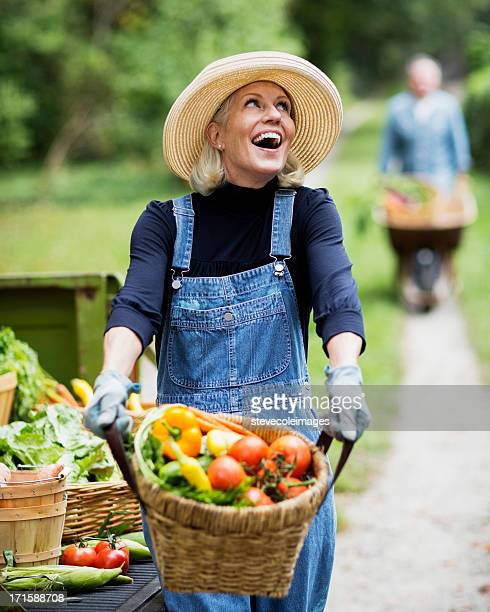 Mature Woman With Man Pushing Cart Full Of Vegetables.