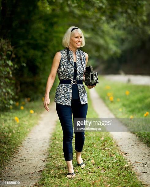 Mature Woman With Press Camera At Park.