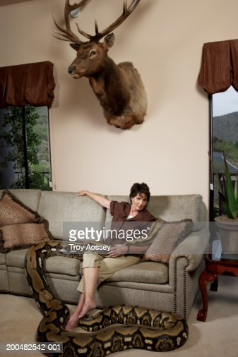 Mature woman with python sitting on couch in living room