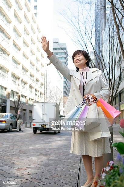 Mature woman with shopping bags, hailing for taxi by the street