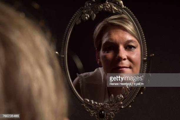 Mature Woman With Short Blond Hair Looking In Mirror Against Black Background