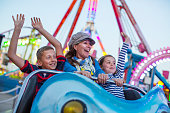 Mature woman with son and daughter on fairground ride