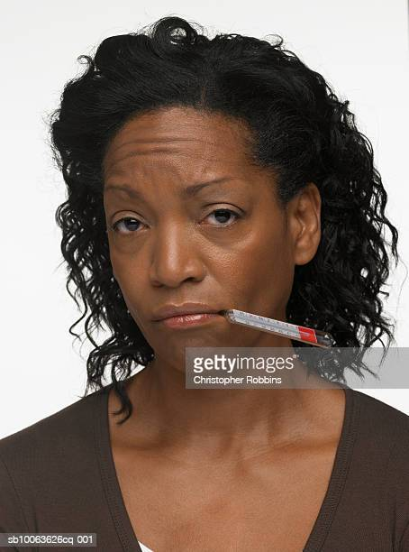 Mature woman with thermometer in mouth, portrait