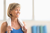 Happy mature woman with towel around neck looking away at home