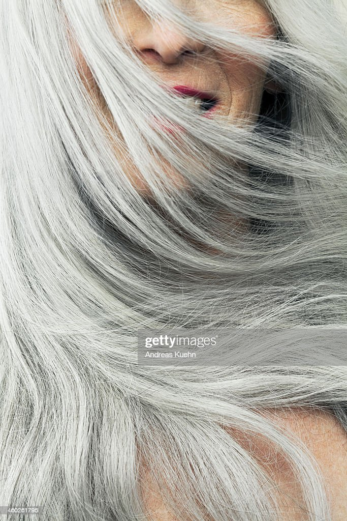 Mature woman with wind blown gray hair, cropped.