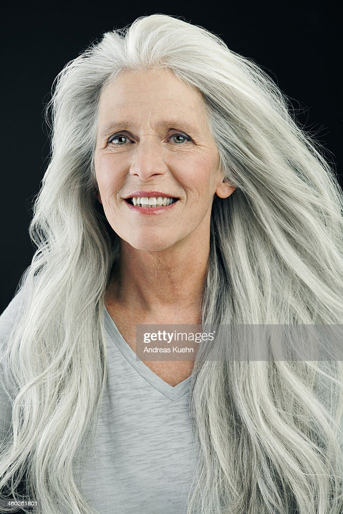 Mature woman with wind blown, long, gray hair.