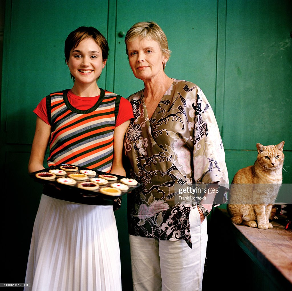 Mature woman with young woman holding tray of tarts, portrait : Stock Photo