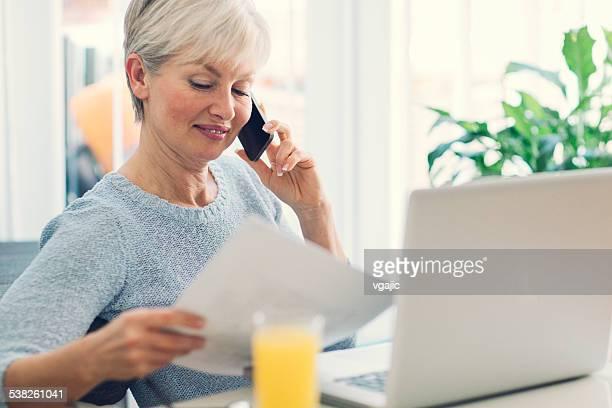 Mature femme travaillant à la maison.
