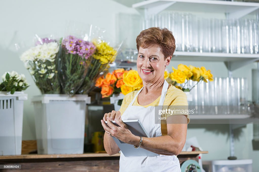 Mature woman working in flower shop using digital tablet : Stock Photo