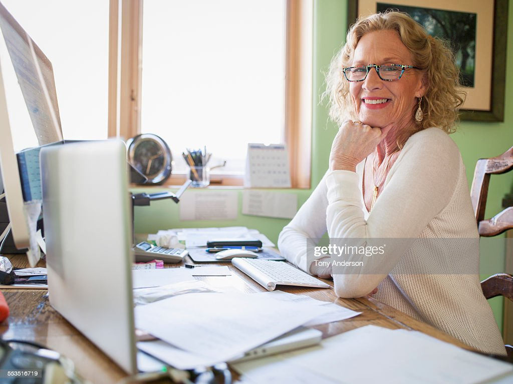 mature woman working in home office stock photo
