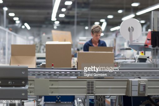 Mature woman working in paper packaging factory