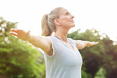 Mature woman doing yoga at park and looking away. Senior blonde woman enjoying nature during a breathing exercise. Portrait of a fitness woman stretching arms and looking away outdoor. 'r