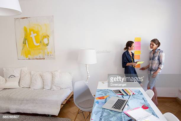 Mature women at home leaning against wall talking