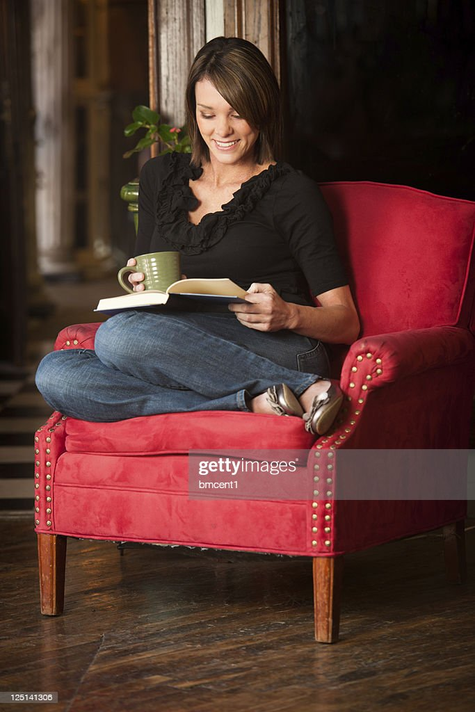 Mature women curled up with a good book and coffee