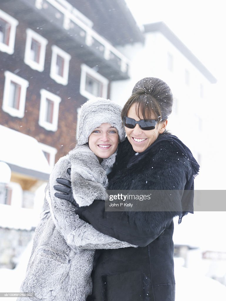 Mature women embracing young women, smiling, portrait : Stock Photo