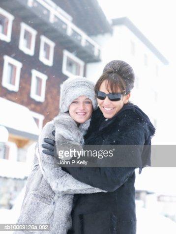 Mature women embracing young women, smiling, portrait : Stock Photo