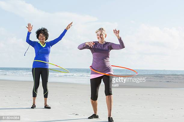 Mature women exercising on beach wth hoola hoops