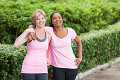 Multi-ethnic mature women (40s) in pink workout clothing.