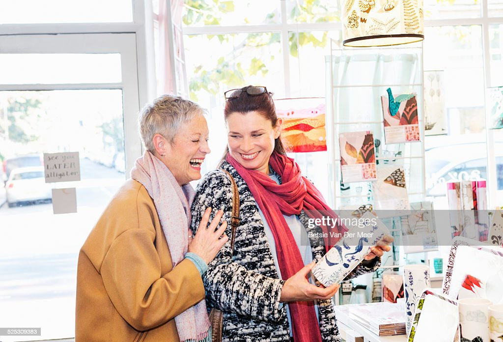 mature women laughing, looking at vase in shop.