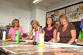 Mature women painting in art classroom, laughing