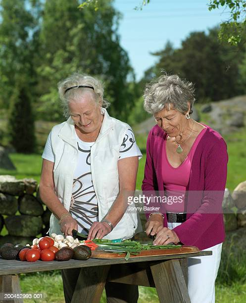 Mature women preparing food in garden, smiling